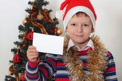 Junge, der Grußkarte hält christmastime Lizenzfreies Stockfoto