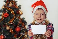 Junge, der Grußkarte hält christmastime Stockfotos