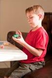 Junge, der hölzernes Auto mit Malerpinsel malt Lizenzfreie Stockfotos