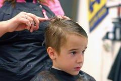 Junge, der Haarschnitt erhält stockbild