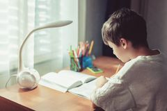 Junge, der Hausarbeit tut oder zu Hause lernt lizenzfreie stockbilder