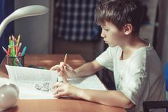 Junge, der Hausarbeit tut oder zu Hause lernt stockfotos