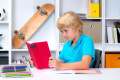 Junge, der Hausarbeit tut und ein Buch liest Lizenzfreie Stockfotos