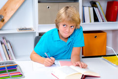 Junge, der Hausarbeit tut und ein Buch liest Lizenzfreies Stockbild