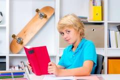 Junge, der Hausarbeit tut und ein Buch liest Stockbilder