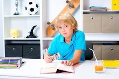 Junge, der Hausarbeit tut und ein Buch liest Lizenzfreies Stockfoto