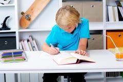 Junge, der Hausarbeit tut und ein Buch liest Stockfoto