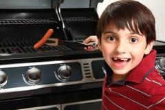 Junge, der herauf ein Würstchen grillt Lizenzfreie Stockfotografie