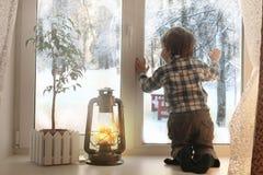 Junge, der heraus auf einem weißen Fensterbrett und Blicken das Fenster sitzt Stockfotos