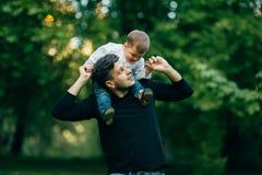 Junge, der heraus Hände während sein Vater trägt ihn auf Schultern ausdehnt Stockfoto
