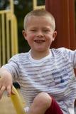 Junge, der heraus am Schulhof-Spielplatz hängt Stockfotografie