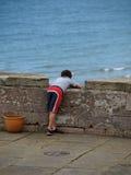 Junge, der heraus zum Meer schaut Stockfoto