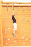 Junge, der am Hindernislauf hängt Stockfotografie