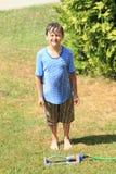 Junge, der hinter Berieselungsanlage steht Lizenzfreies Stockbild