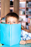 Junge, der hinter Buch sich versteckt Stockfoto