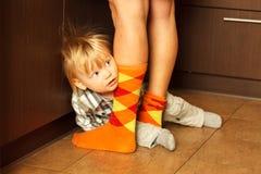 Junge, der hinter Mutter sich versteckt Lizenzfreies Stockfoto