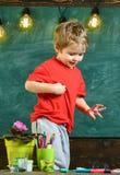 Junge, der hinter der Tabelle mit eingemachten Blumen, Märkten und Bleistiften steht Nettes, blondes Kind, das unten schaut Lizenzfreie Stockbilder