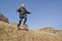 Junge, der hinunter einen Hügel an der Festung läuft Stockbild