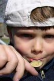 Junge, der Honig isst Stockbild
