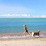 Junge, der Hund auf einer Seeküste spielt Lizenzfreie Stockfotografie