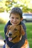 Junge, der Hund umarmt Stockfotos