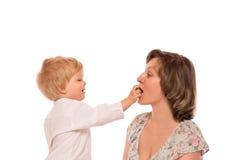 Junge, der ihrer Mutter eine Süßigkeit gibt Stockfotografie