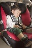 Junge, der im Autositz schläft Stockfotografie