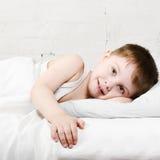 Junge, der im Bett lächelt Stockfotos