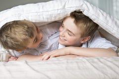 Junge, der im Bett unter einer weißen Decke oder einer Bettdecke sich versteckt lizenzfreies stockbild