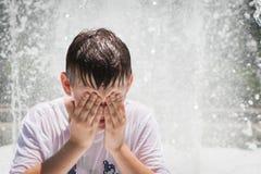 Junge, der im Brunnen spielt Stockbild