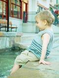 Junge, der im Brunnen spritzt Lizenzfreie Stockbilder