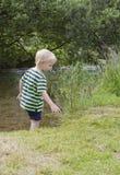 Junge, der im flachen Fluss steht Stockbild