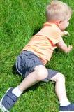 Junge, der im Gras liegt Stockfotografie