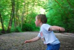 Junge, der im Holz spielt Lizenzfreies Stockbild