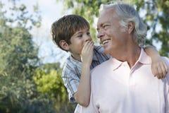 Junge, der im Ohr des Großvaters flüstert lizenzfreies stockfoto