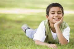 Junge, der im Park sich entspannt Stockfotos