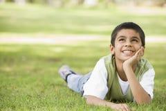 Junge, der im Park sich entspannt Stockfotografie