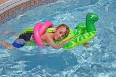 Junge, der im Pool sich entspannt Stockbilder
