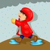 Junge, der im Regen spielt Stockbild