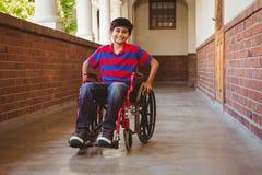Junge, der im Rollstuhl im Schulkorridor sitzt Lizenzfreies Stockfoto