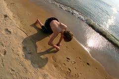 Junge, der im Sand auf Strand spielt Stockbild