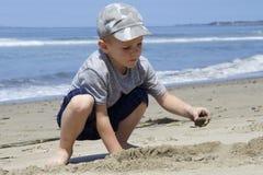 Junge, der im Sand nahe dem Pazifischen Ozean spielt Lizenzfreies Stockfoto