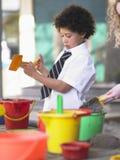 Junge, der im Sand Pit In School Playground spielt Stockbild