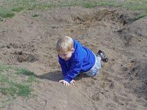 Junge, der im Sand spielt Stockfotos