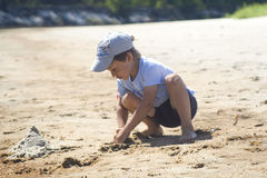 Junge, der im Sand spielt Stockbild