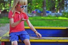 Junge, der im Sandkasten sitzt Lizenzfreies Stockfoto