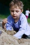 Junge, der im Sandkasten spielt Lizenzfreie Stockbilder