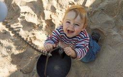Junge, der im Sandkasten spielt Stockbild
