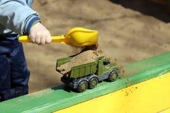 Junge, der im Sandkasten spielt Stockbilder
