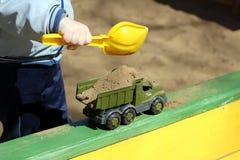 Junge, der im Sandkasten spielt Stockfoto